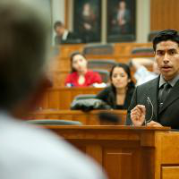 Miguel Zavala, participant in the King Hall Outreach Program, argues before a panel of judges in a mock courtroom