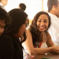 Two students smile at each other in a sunny classroom.