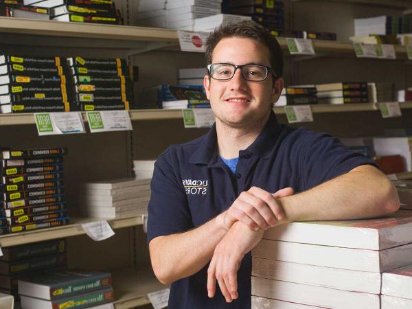 Male student leaning on a stack of books